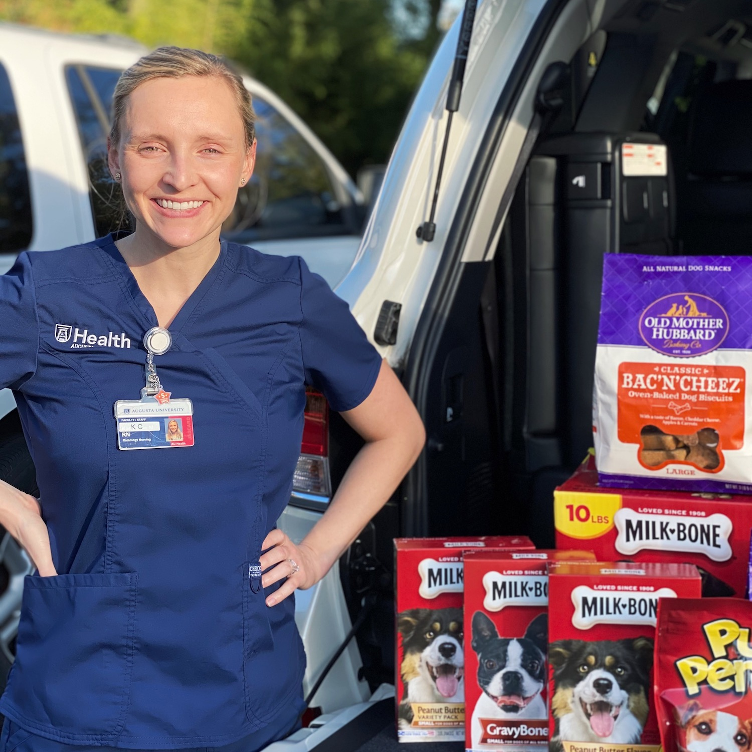 Woman in blue scrubs standing with boxes of dog treats